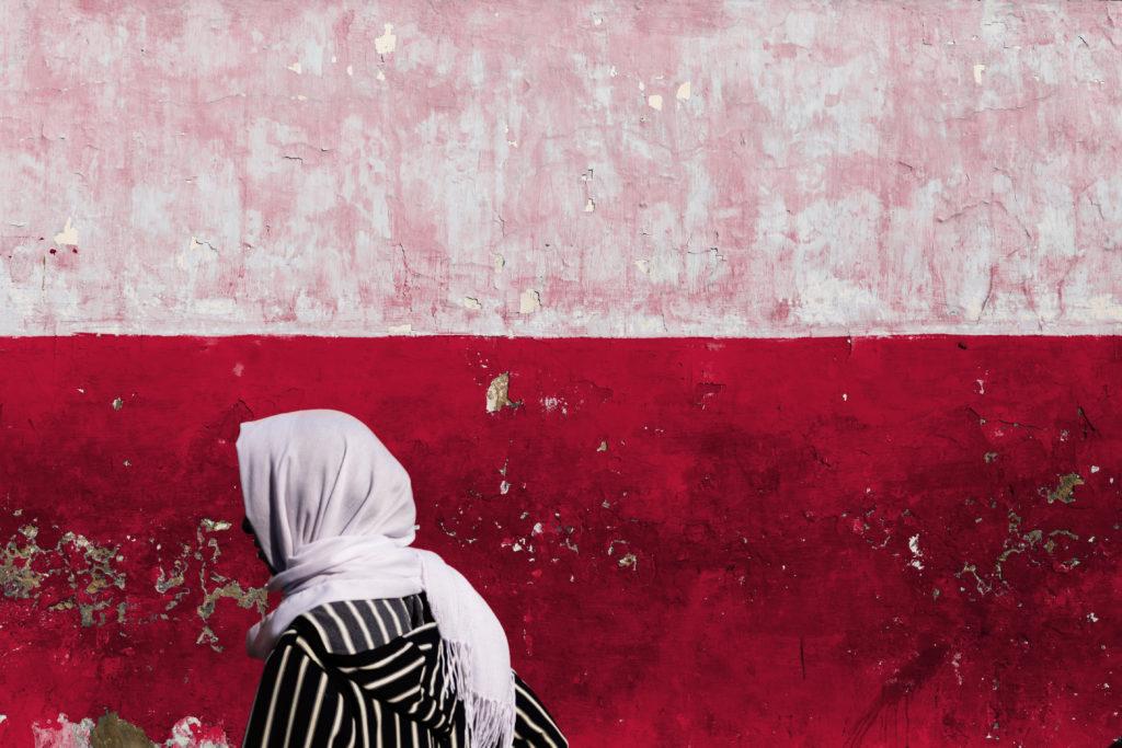 Une hijabi marchant à pas assurés sur une voie pour elle tracée, à contre-courant de autres